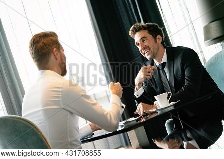 Two Business People Sitting At Coffee Shop Discussing Project