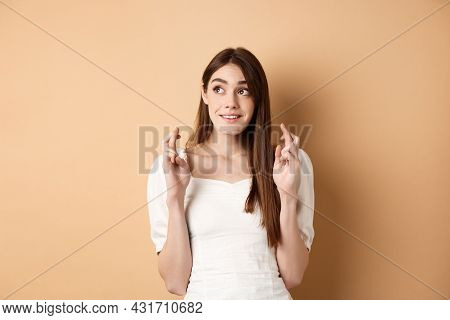 Hopeful Cute Woman Looking At Upper Left Corner Space And Cross Fingers For Good Luck, Making Wish,