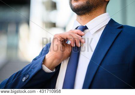 Closeup of a businessman adjusting his necktie