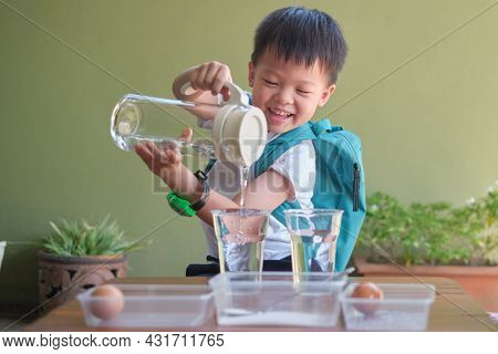 Happy Asian School Kid Studying Science, Pouring Water To Do Fun And Easy Floating Egg Science Exper