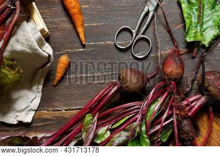 Raw Beetroot With Tops And Carrots On A Rough Wooden Surface. Close-up, Top View, Horizontal