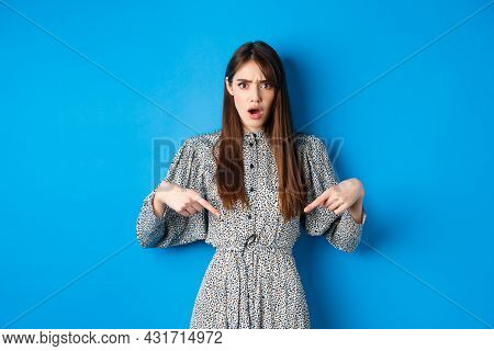Shocked And Offended Young Woman In Dress Frowning, Gasping And Pointing Fingers Down At Insulting P