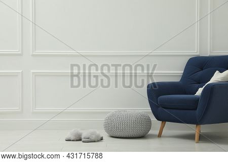 Knitted Pouf, Fuzzy Slippers And Armchair Near White Wall Indoors. Space For Text