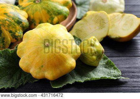 Fresh Ripe Yellow Pattypan Squashes With Leaves On Black Wooden Table, Closeup