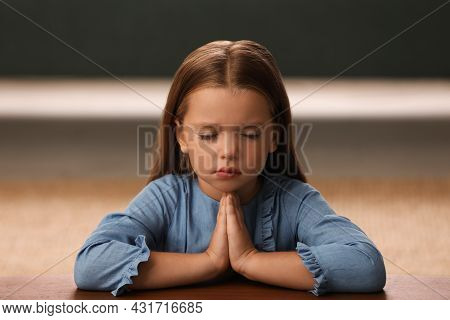 Cute Little Girl With Hands Clasped Together Praying At Table Indoors