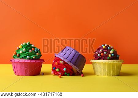 Dropped Cupcake Among Good Ones On Yellow Table. Troubles Happen