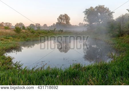 Early morning on small lake in forest. Mist over water.