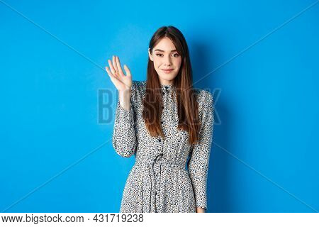 Cute Smiling Woman Waving Hand To Greet You, Saying Hello With Shy Grin, Standing In Dress Against B