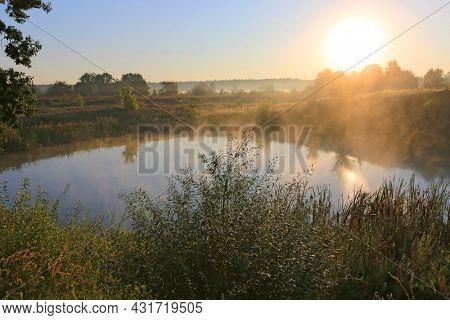 Morning sunrise over small alke in steppe