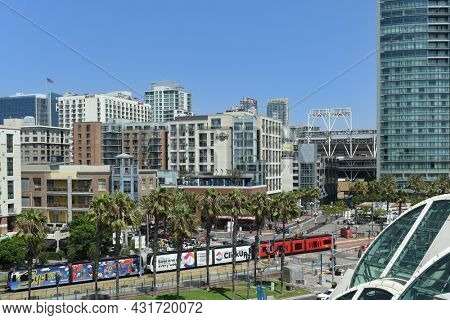 SAN DIEGO, CALIFORNIA - 25 AUG 2021: Downtown San Diego with the Red Line Trolley passing between the Convention Center and the Gaslamp Quarter.
