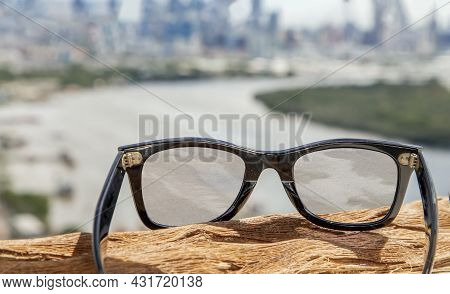 Black Eyeglass On A Reflective Surface. View Through The Lens Of Glasses That Look At The Chao Phray