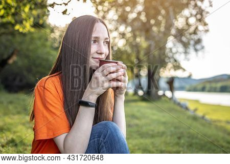 Attractive Young Woman With A Cup Of Tea Is Sitting On The Grass In The Forest By The River And Enjo