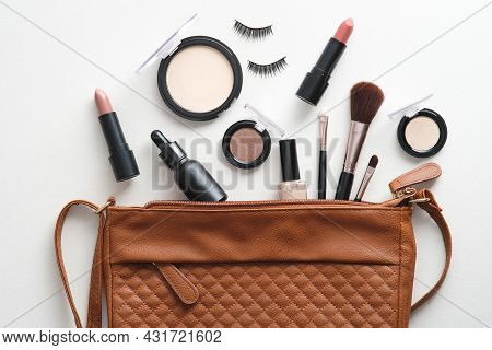 Cosmetic Pouch With Professional Decorative Cosmetics And Makeup Tools On White Background. Top View