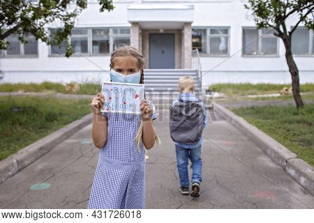 Elementary School Girl In Medical Mask Holds Picture With Back To School Message. Boy With Backpack