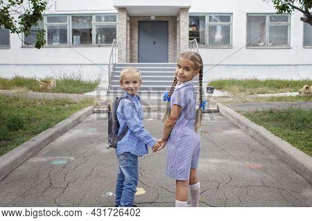 Back To School. Happy Siblings With Backpacks, Elementary School Kids, Staying Near School Doors Bef