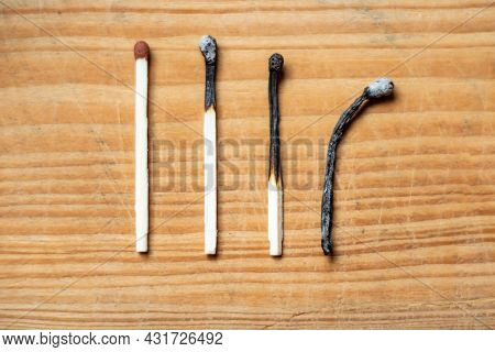 Row Of Burnt Matches And Whole One On Wooden Background, Top View,closeup. Human Life Phases Concept