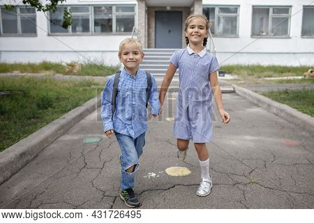Back To School. Happy Siblings With Backpacks, Elementary School Kids, Running From The School After
