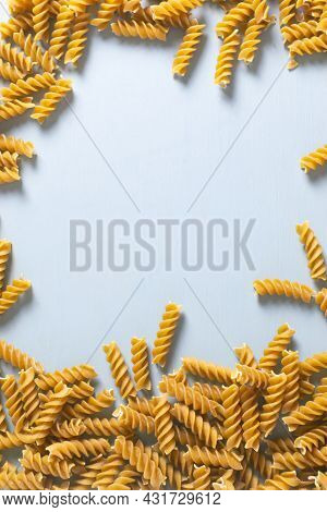 Raw Fusilli Pasta On A Gray Background. Whole Grain Pasta. Top View. Healthy Nutrition Concept. Vert
