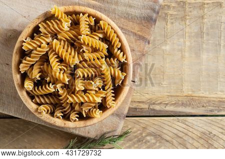 Raw Fusilli In A Wooden Bowl On A Cutting Board On A Wooden Table. Rustic Style. Horizontal Orientat