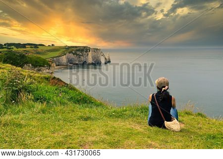 Woman contemplating dramatic sunset over the Etretat bay in Normandy, France