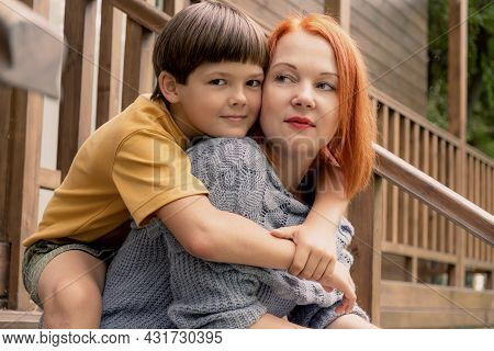 Eight-year-old Boy Hugs His Mother By The Shoulders. Mom And Son Are Sitting On The Wooden Porch Of