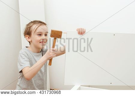 Boy Assembles A Bookshelf Himself. Child With Hammer. Son Helping His Dad To Assembling New Furnitur