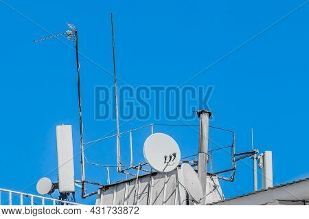 Tv And Mobile Signal Old System Of Technologies On The Roof Of The Building Against The Blue Sky.