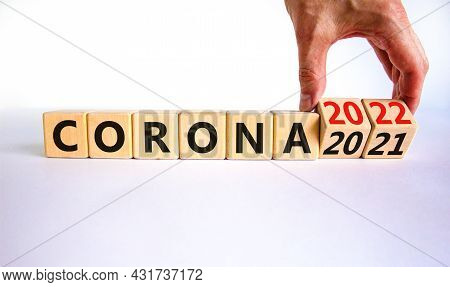 Symbol Of Covid-19 Pandemic In 2022. Doctor Turns Wooden Cubes And Changes Words 'corona 2021' To 'c