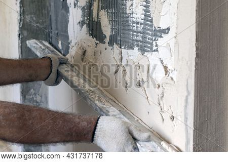 Worker Applies Plaster To The Wall. The Worker Levels The Plaster With A Leveler