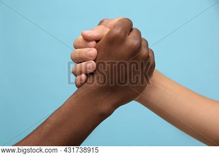 Men Clasping Hands On Light Blue Background, Closeup