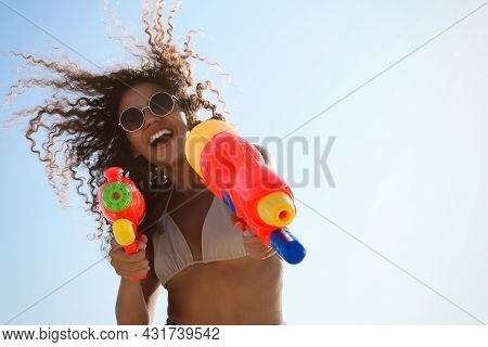 African American Woman With Water Guns Against Blue Sky, Low Angle View. Space For Text