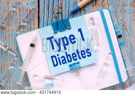 Diabetes Type 1. The Sticker Is Attached To The Notebook With A Clerical Clip. Notebook On A Wooden