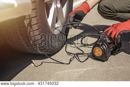 Tire Pump Inflating Car Wheel. Tyre Inflator In Male Hands, Checking Pressure With Manometer.