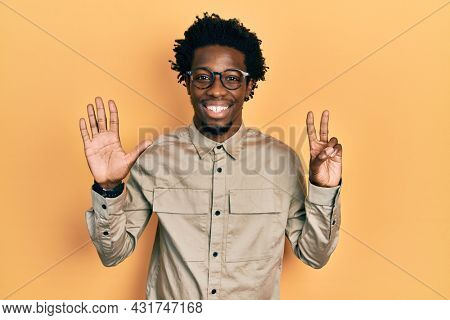 Young african american man wearing casual clothes and glasses showing and pointing up with fingers number seven while smiling confident and happy.