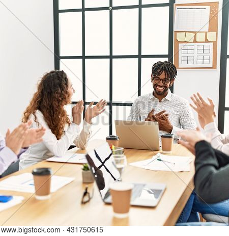 Group of business workers smiling and clapping to partner at the office.