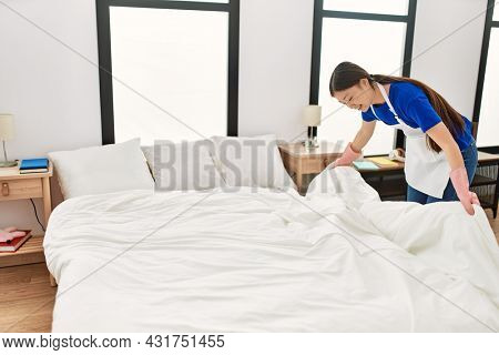 Young chinese housewife make bed at home.