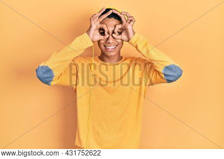 Young african american guy listening to music using headphones doing ok gesture like binoculars sticking tongue out, eyes looking through fingers. crazy expression.