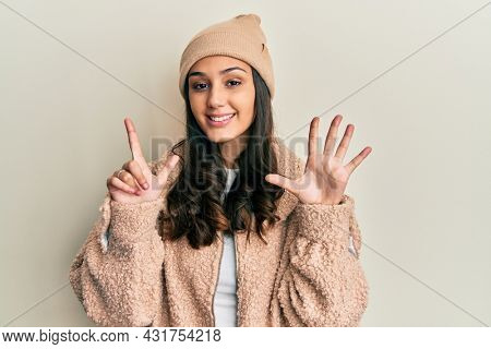 Young hispanic woman wearing wool sweater and winter hat showing and pointing up with fingers number seven while smiling confident and happy.