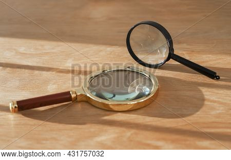 Two Magnifying Glasses On Wood Desk With Daylight. Concept Of Observation, Exploration, Study And Re