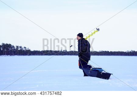 Ice Fishing. Fisherman Fishing On A Winter Lake Against A Background Of Forest.