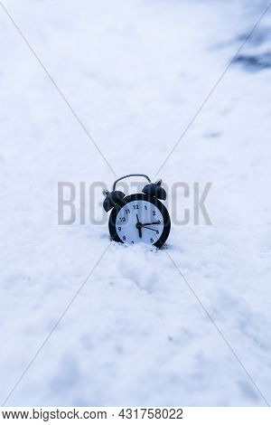 Alarm Clock In Snowy Weather On A Winter Background. Return To Winter Time. Changing The Clock With