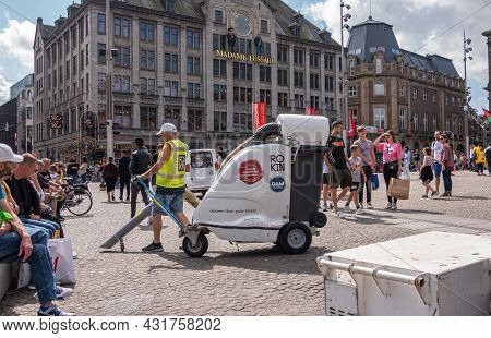 Amsterdam, Netherlands - August 14, 2021: Man With Yellow Security Vest Handles Rolling Industrial V