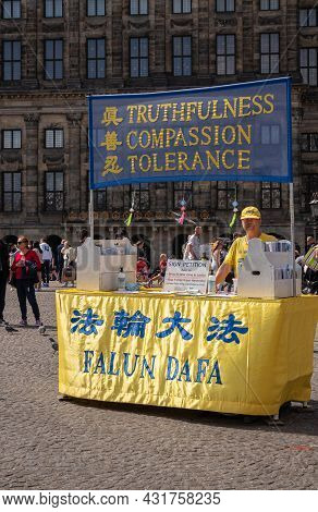 Amsterdam, Netherlands - August 14, 2021: Portrait, Falun Gong Info Booth Distributes Flyers And Sig