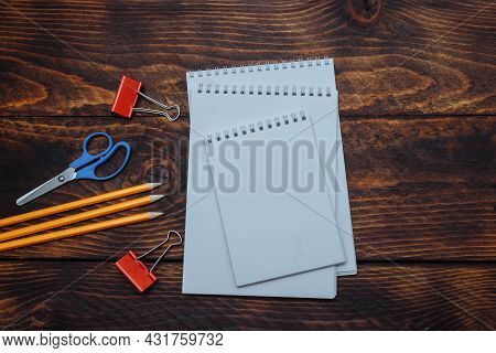 Three Spring-loaded Notebooks With White Paper, Pencils, Scissors, Paper Clips On Brown Wooden Backg