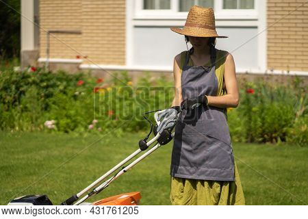 A Young Girl In A Straw Hat Is Mowing A Lawn In The Backyard With An Orange Lawn Mower. A Woman Gard