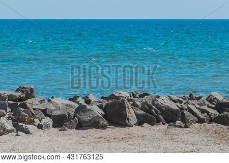 Breakwater Beach Stones On The Sea Coast With Blue Water Against The Background Of The Horizon Line.