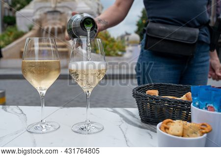 Waiter Pouring Of Brut Champagne Sparkling Wine Into Glasses In Street Cafe In Old Central Part Of C