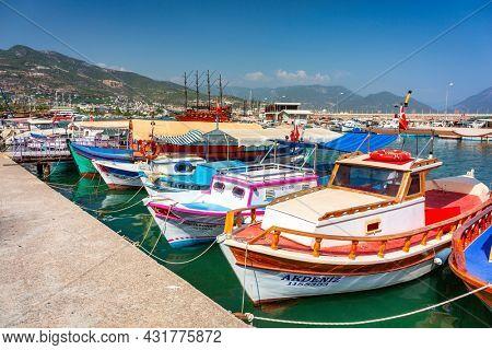 Alanya, Turkey - July 21, 2021: Beautiful colorful boats in Alanya harbor on the Mediterranean Sea, Turkey