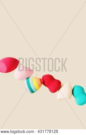 Color Cosmetic Beauty Blender Sponges On Nude Colored Background With Copy Space. Red, Pink, Rainbow