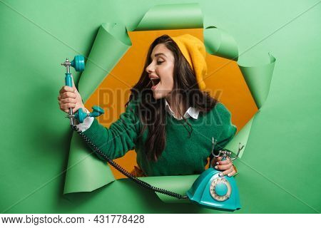 Young white smiling woman peeking out hole isolated on green background talking on a landline phone